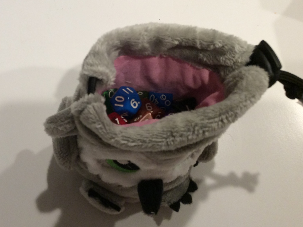 Looking into the drawstring opening of a tiny plush owlbear that is also a dice bag.