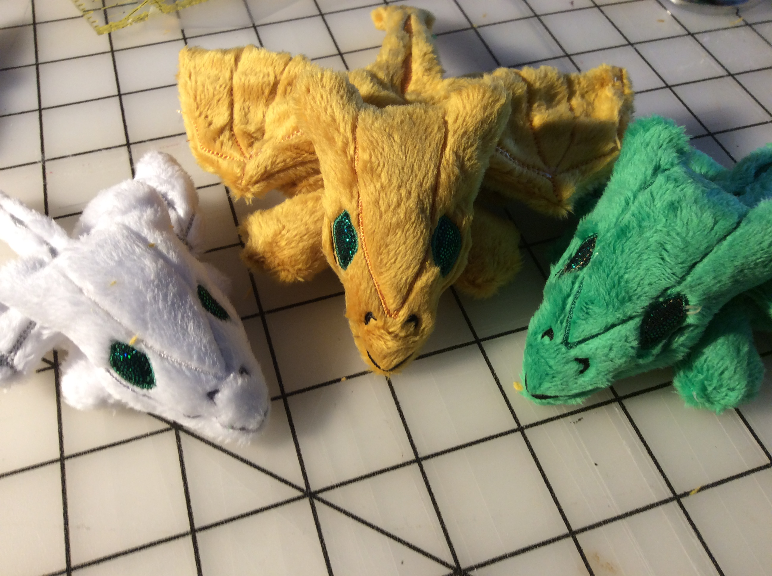 White, gold, and green tiny plush dragons.