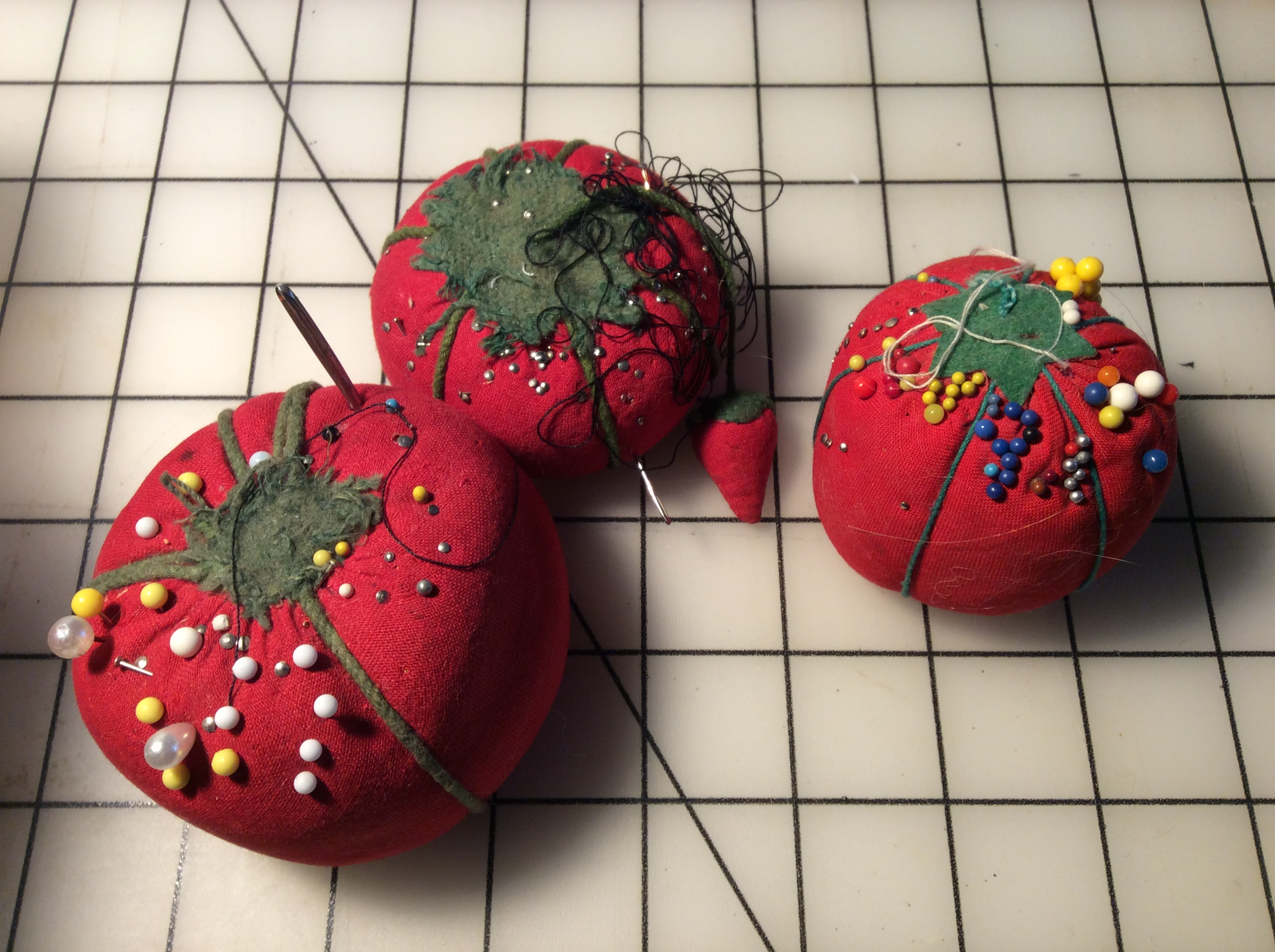 "Three tomato-shaped pincushions, one with an attached ""strawberry."""