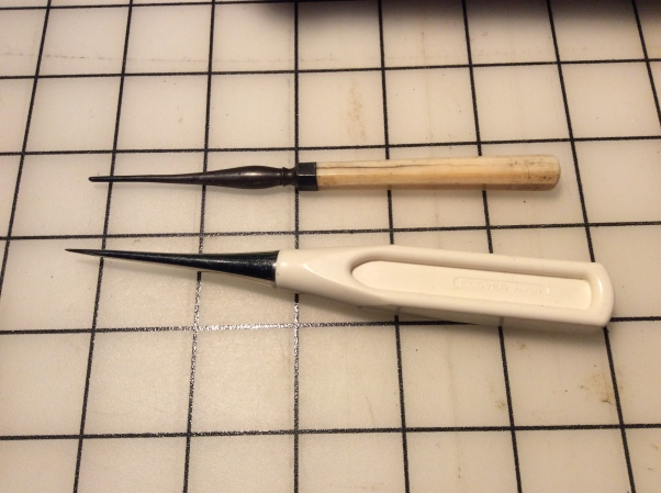 An antique tailor's awl compared to a new one.