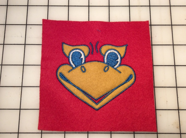 Embroidered Kansas Jayhawk mascot face on a piece of felt