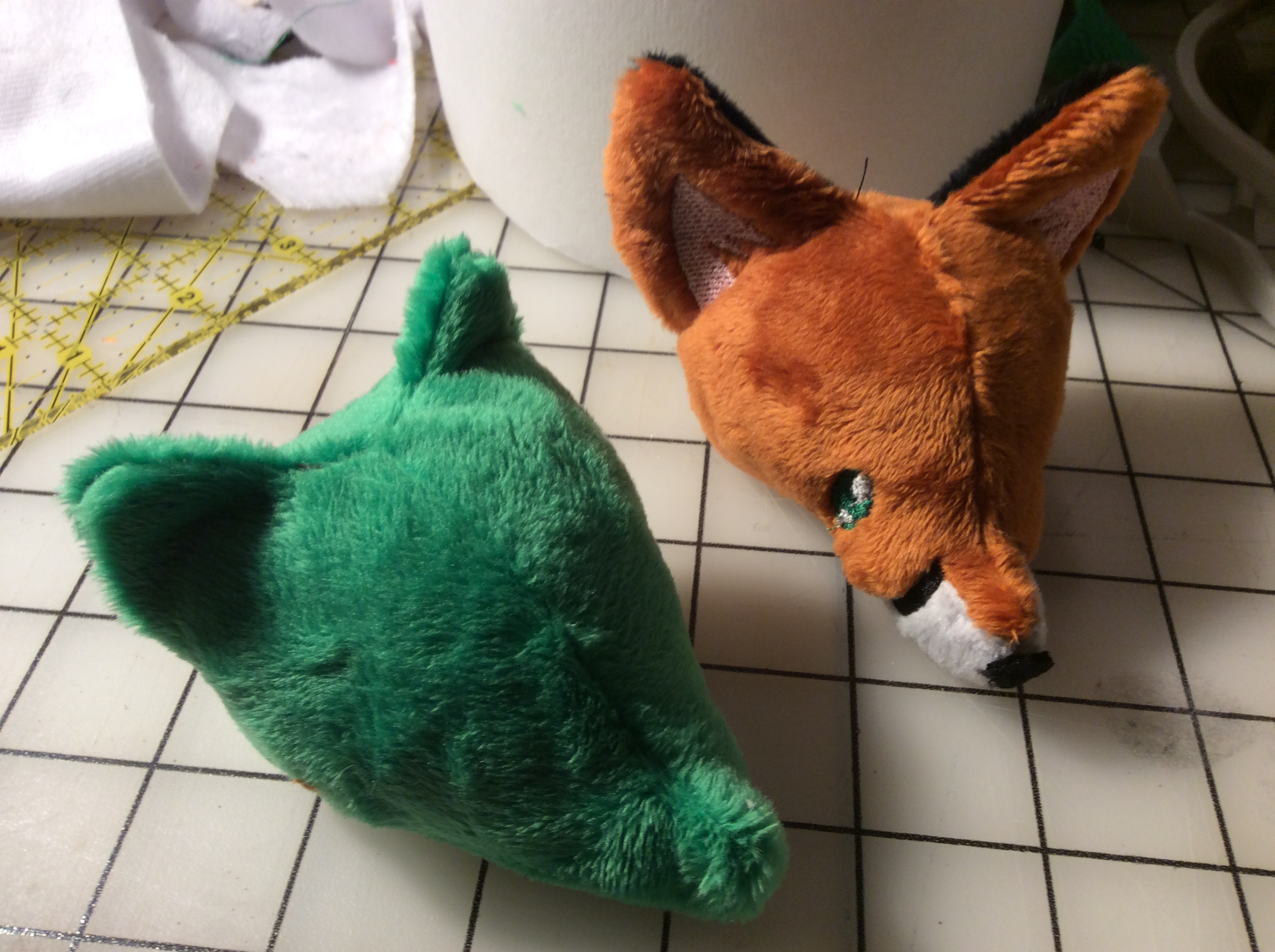 A blank green not-a-raccoon head next to a more finished fox head.