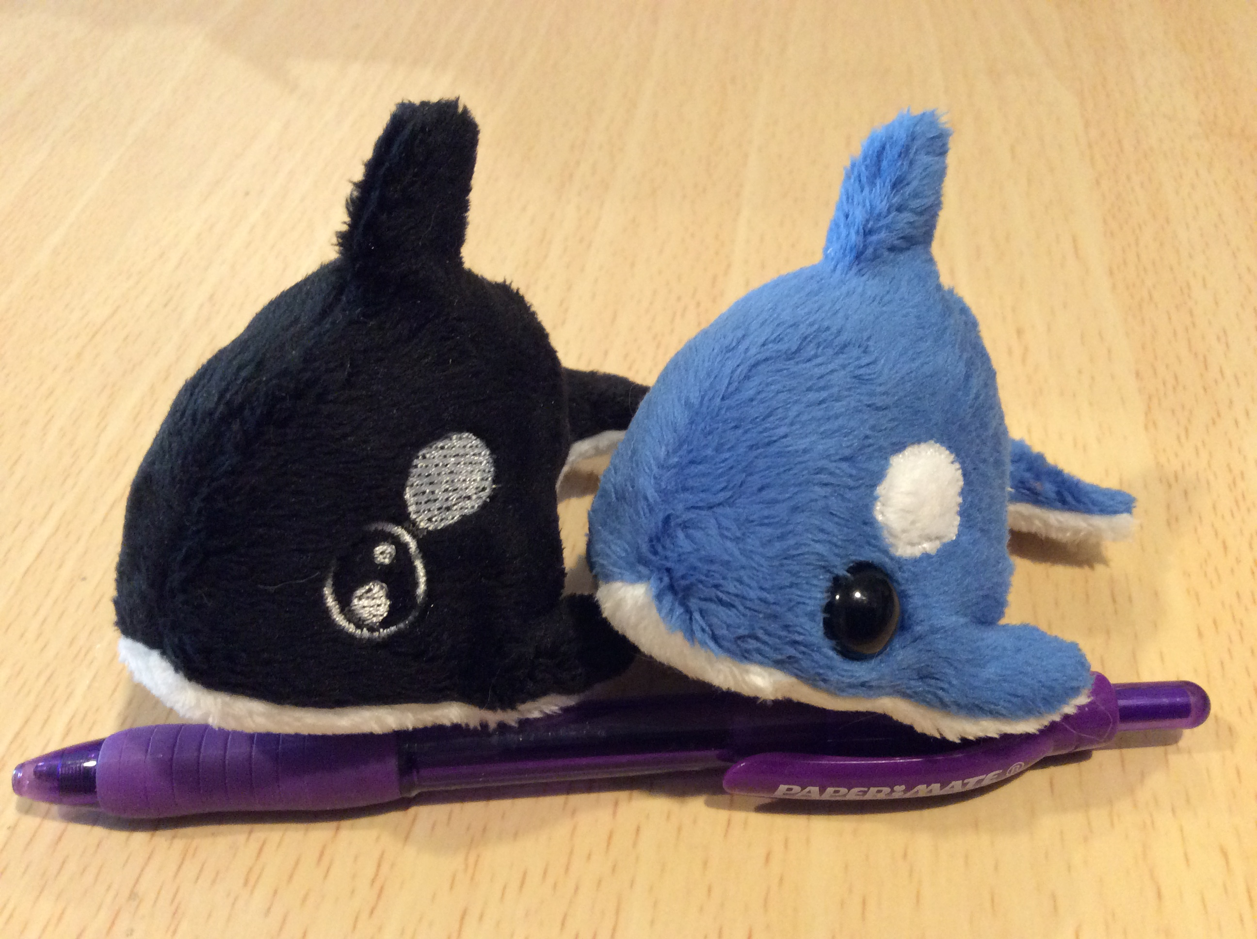 A pair of tiny plush killer whales, with a pen for scale.